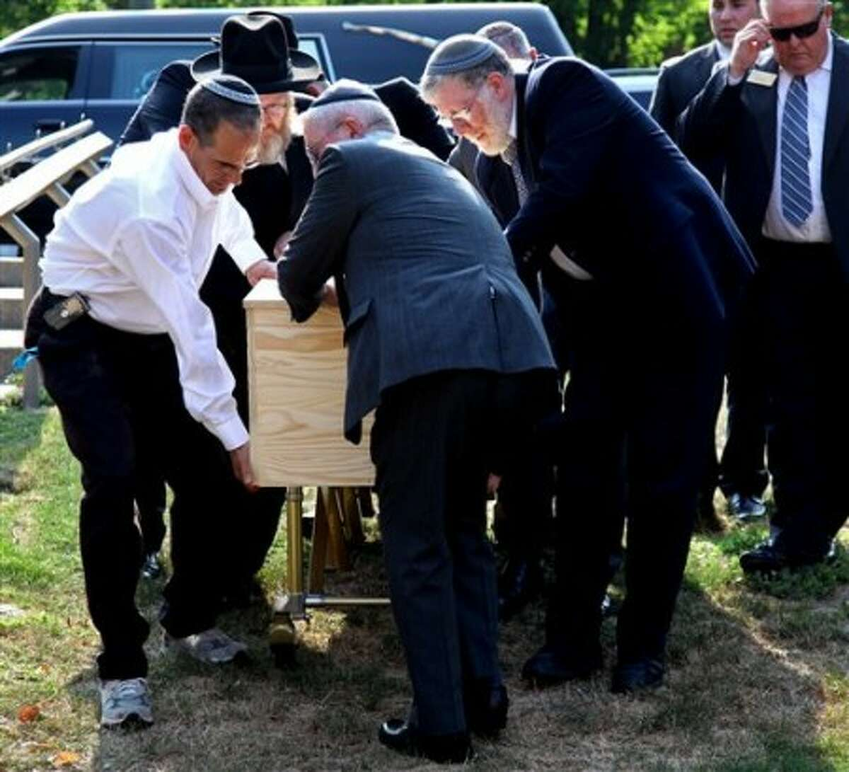 The casket containing Louis Felder is carefully wheeled towards the Congregation Agudath Sholom before the funeral Wednesday, Aug. 4, 2010, in Stamford, Conn. Felder was one of eight people killed Tuesday when Omar Thornton opened fire after a disciplinary hearing at a beverage distributorship where he worked in Manchester, Conn. (AP Photo/Craig Ruttle)