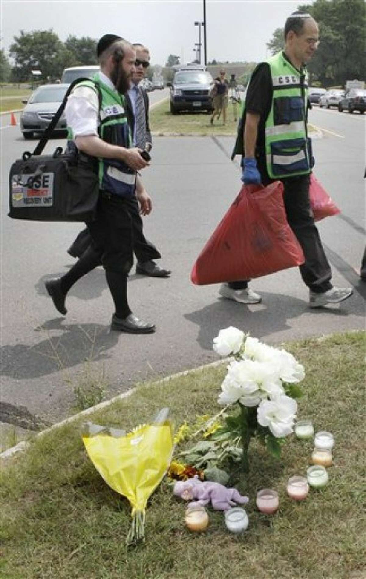 Rabbi Mayer Berger, left, follows a man carrying bags of bloodied fabric past a makeshift memorial outside the Hartford Distributors building, where a gunman killed eight people and himself on Tuesday, in Manchester, Conn., Wednesday, Aug. 4, 2010. (AP Photo/Charles Krupa)
