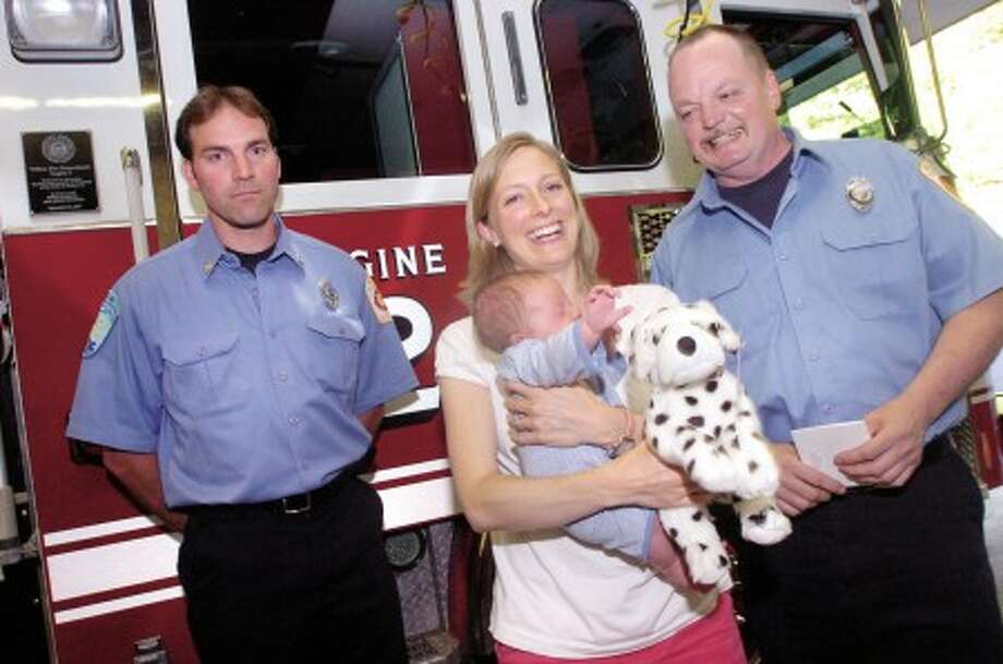Wilton firefighters, Glenn Johnson and Gregg Kitik who delivered Beth Lambert''s baby boy Ian a month ago are honored at the Firehouse headquarters on Wednesday. photo/matthew vinci