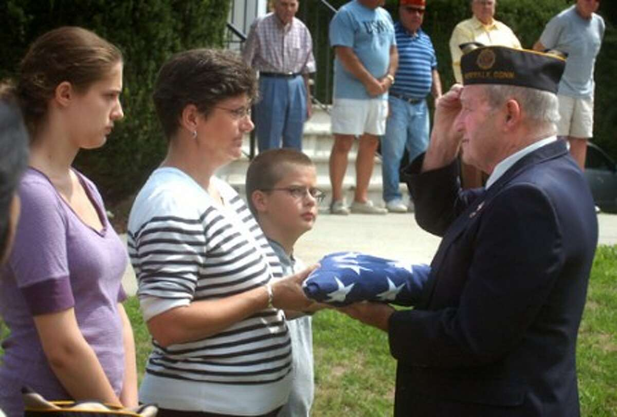 Photo/Alex von Kleydorff. l-r Allyson, Teresa and Michael Wojnoski represent honored veteran Nicholas Pelin and pass his flag to Sergeant at Arms Bob Forbis during a ceremony at The American Legion Post 12 in Norwalk Sunday.