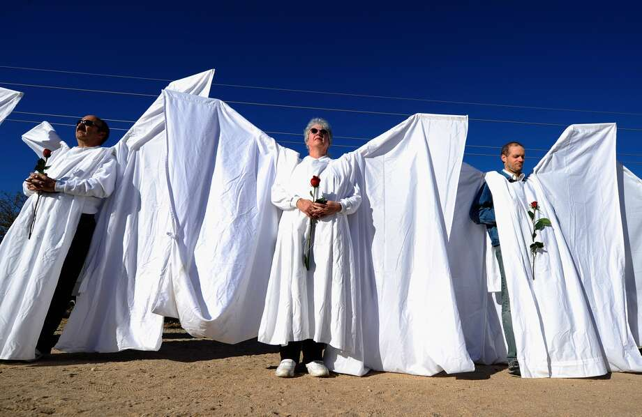 "A group of staff and volunteers from Orlando Shakespeare Theater as well as ​the​ Orlando arts community work together to build ""Angel Wings"" to block Westboro Baptist Church members protesting the funerals of the Orlando shooting victims. When finished, they will look like this. Pictured: Mourners dressed as angels stand across the street from St. Elizabeth Ann Seton church where the funeral service for US District Court Judge John Roll is being held on January 14, 2011 in Tucson, Arizona."