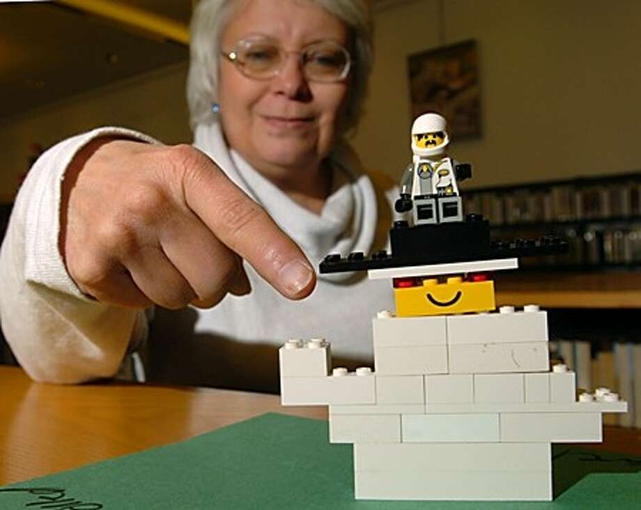 """Lesley Keogh, Children''s Service Assistant at the Wilton Library points out her favorite scupture built by partcipants of the library''s Lego Club entitled, """" Evil Killler Snowman from Outerspace Who Throws SnowBalls and is Also a Robot thet Can Be Controlled"""". Hour photo / Erik Trautmann"""