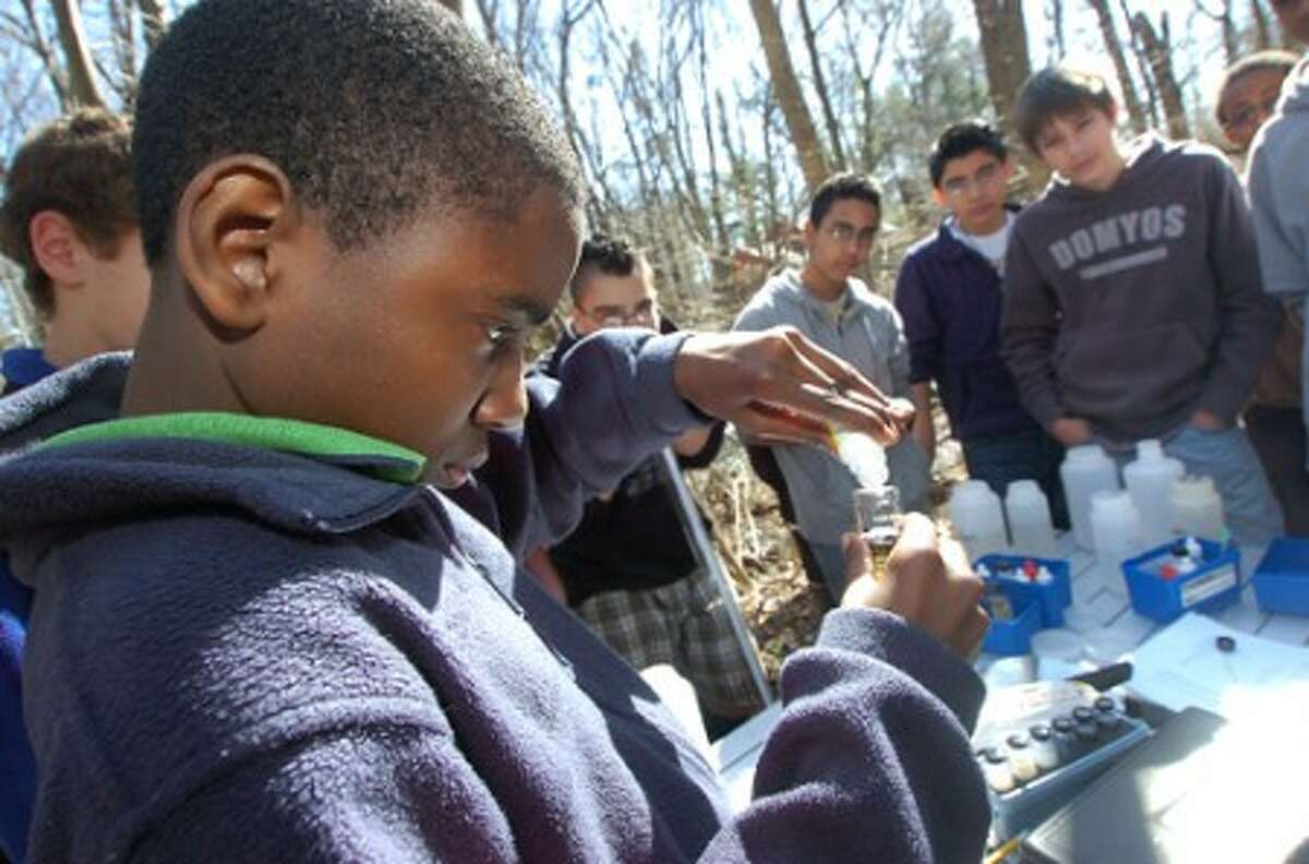 Photo/Alex von Kleydorff. Scofield Magnet school''s Gabriel Joseph tests a sample of The Rippowam river for water quality during a program with Soundwaters on Thursday.
