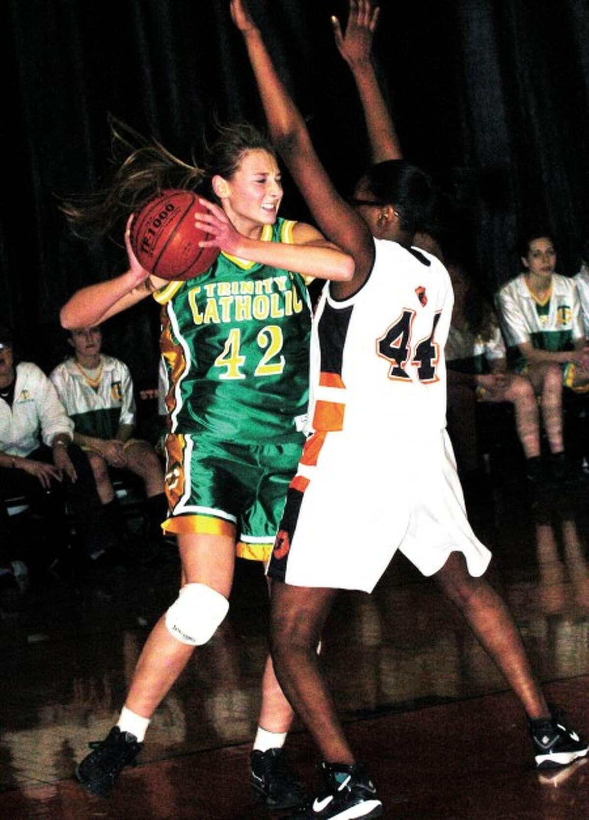 Trinity girls basketball player Mackenzie Griffin (42)battles Stamford''s Jasmine Jones during Tuesday''s game. Photo by Matthew Vinci