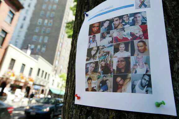 A sign with photos of victims of the Orlando nightclub shootings is tacked to a tree across the street from the Stonewall Inn, birthplace of the modern gay rights movement where there is a makeshift memorial to the Orlando victims, Wednesday, June 15, 2016, in New York. (AP Photo/Kathy Willens)