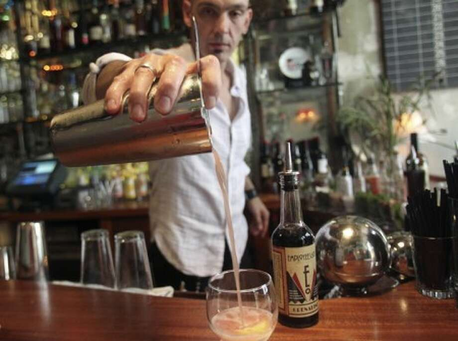 Dushan Zaric mixes a cocktail called The Billionaire, which among other ingredients contains bourbon, absinthe and grenadine, at the Macao Trading Co. in New York. (AP Photo/Seth Wenig)