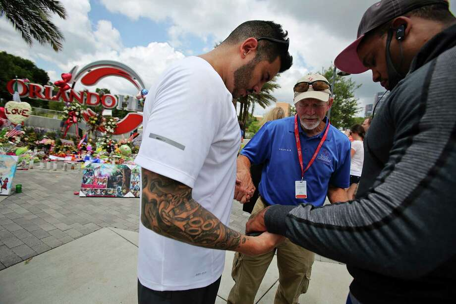 Carl Hill, center, with the Billy Graham Rapid Response Team prays with Ricky Padilla, left, and Nathan Watson, right, next to a memorial for the victims of the Pulse nightclub attack. Photo: Jacob Langston, MBO / Orlando Sentinel