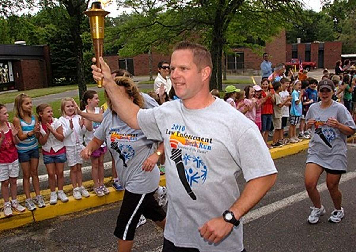 Wilton police lieutenant Steve Brennan bears the Special Olympic torch as he passes by Miller Driscoll school in Wilton Friday morning. Hour photo / Erik Trautmann
