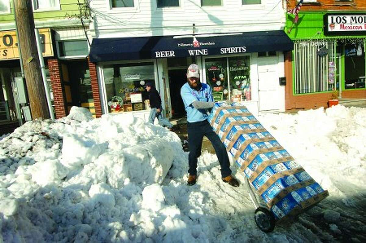 Photo/Alex von Kleydorff. Bob Couture with Star Distributors, navigates the snow filled parking lot at Liberty Square to make a beer delivery to Ninety 9 Bottles Liquor store on Wednesday.