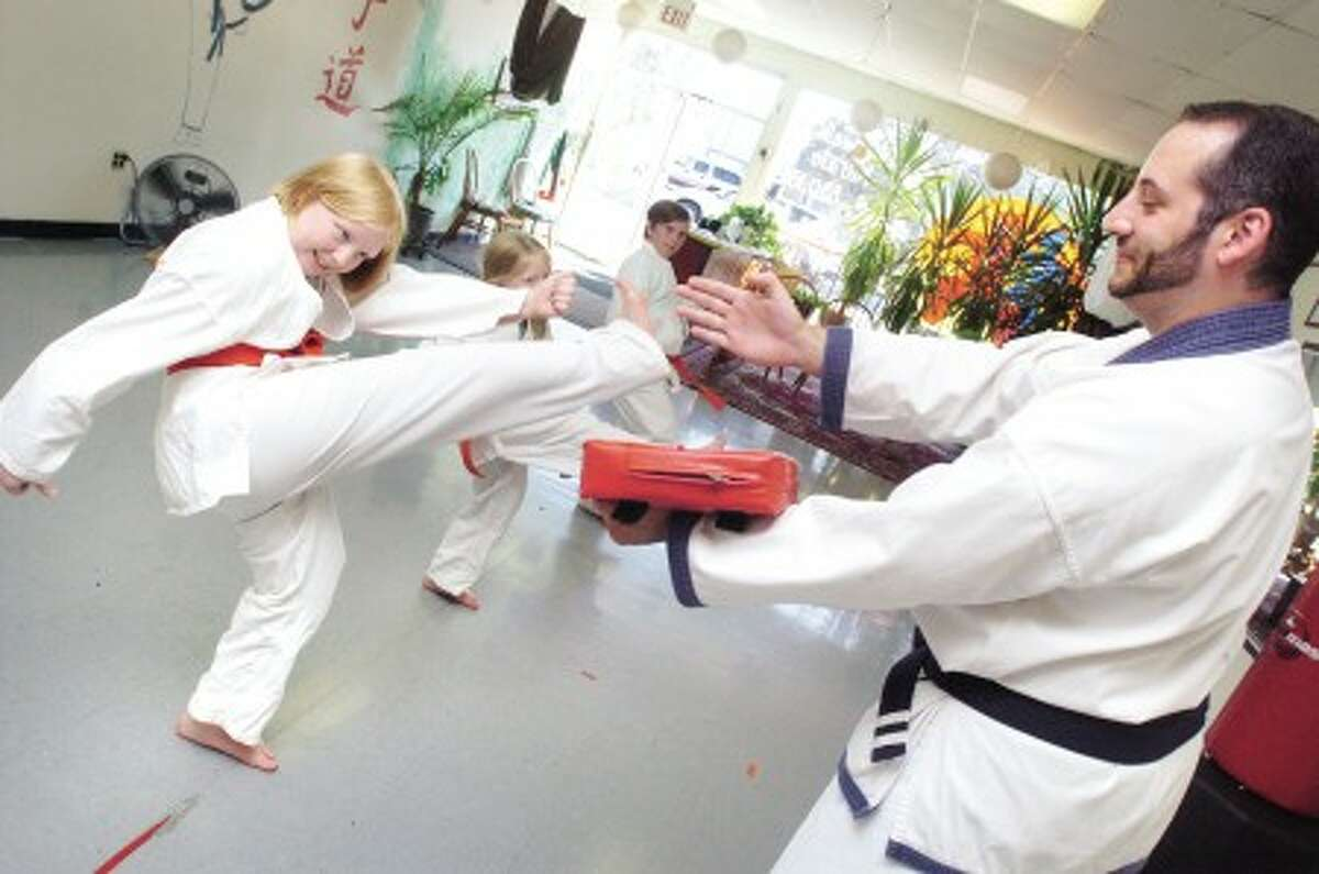 David Palmary works out with 12 year old student Astrid Stephenson at Norwalk Karate. David and co-owner Shelley Lindstrom also teach a self defense workshop at the Wilton Library. photo/matthew vinci