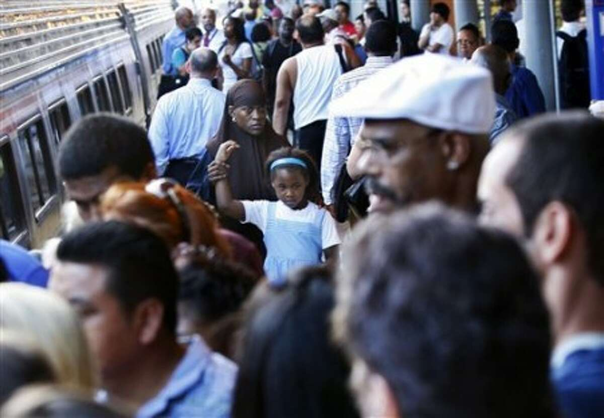 AP Photo - People wait to board an Amtrak train on Friday.