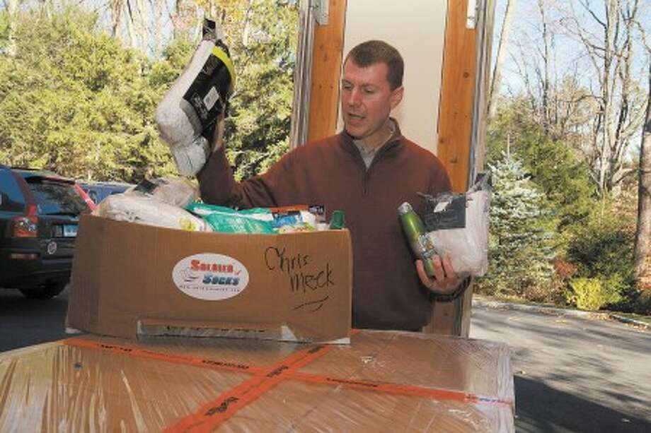 Chris Meek, founder of Soldier Socks, explains his organization and shows some of the items they send to soldiers in Afghanistan and and Iraq at his home in Stamford Sunday afternoon. Hour Photo / Danielle Robinson