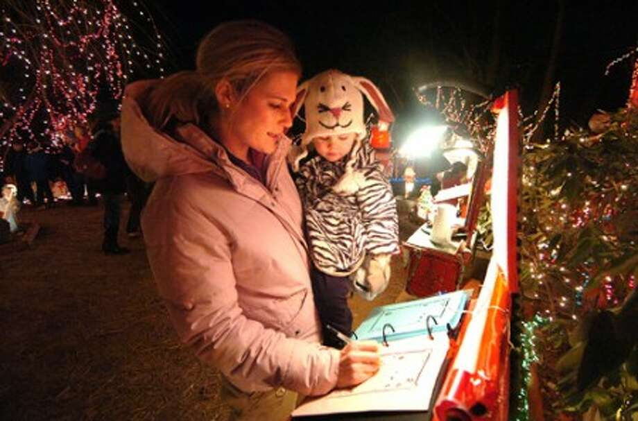 Photo/Alex von Kleydorff. Stephanie Forero holds on to 2 yr old Finley as she has mom write her wishes down for Santa.