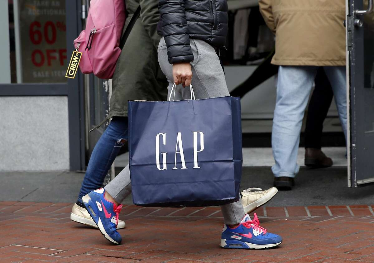A shopper carries a Gap bag in front of the store on Market Street in San Francisco in 2015.