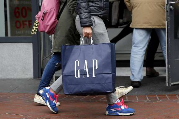 A shopper carries a Gap bag in front of the store on Market Street in San Francisco, California, on Wednesday, Dec. 30, 2015.