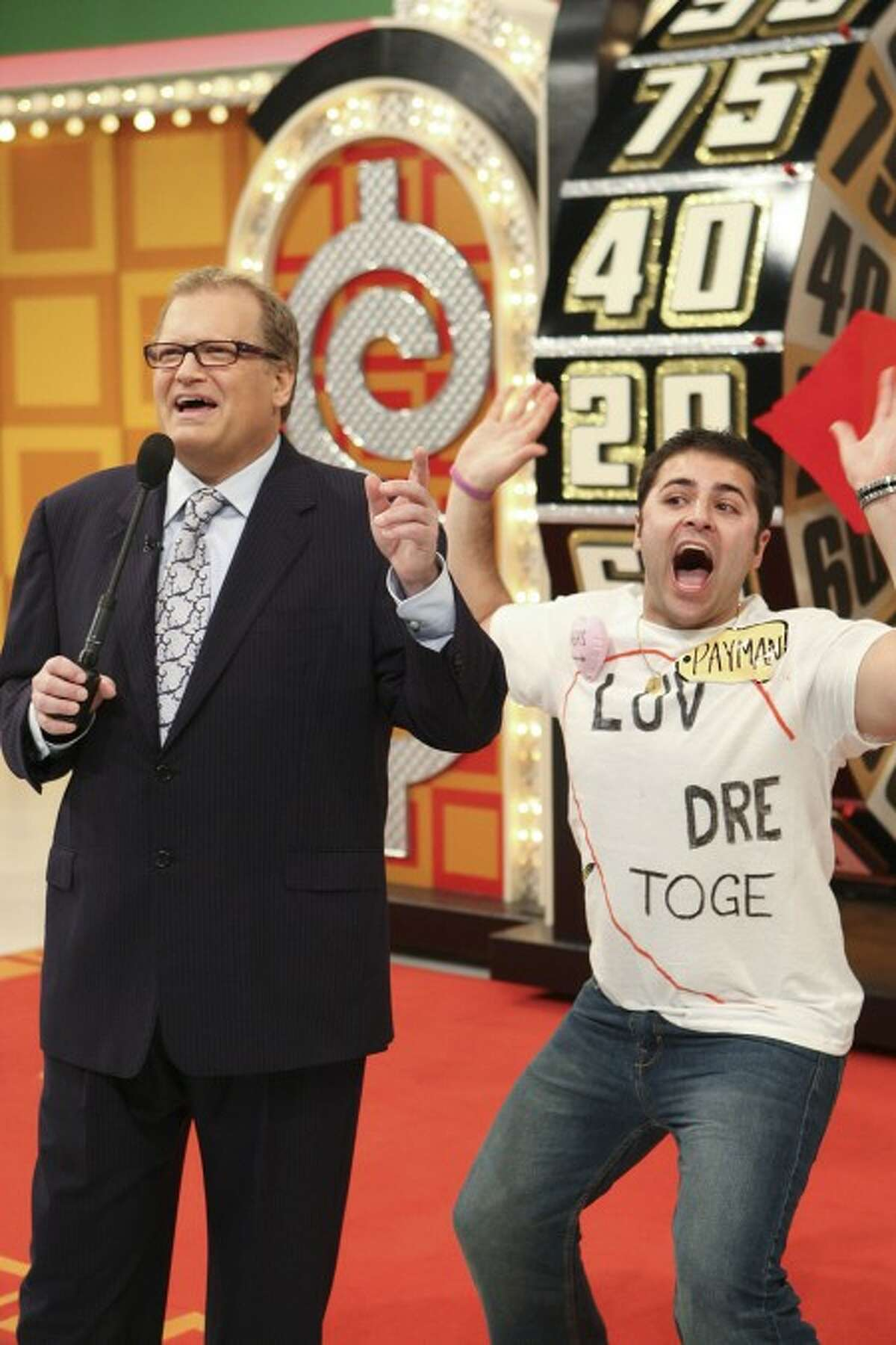 Host Drew Carey, left,stands with contestant Payman Farrokhgar on stage during