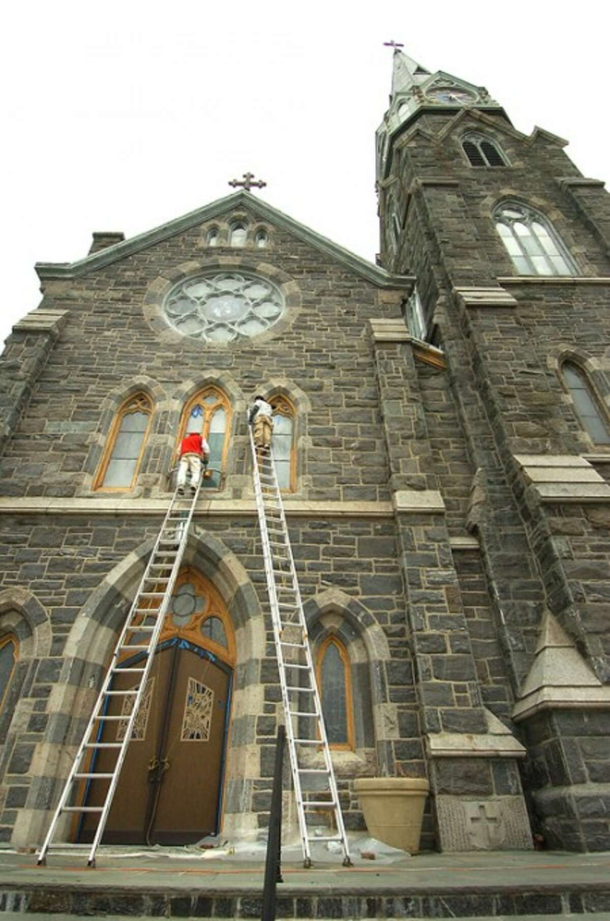 Photo/Alex von Kleydorff. Workers remove old paint from window trim during exterior work as part of a three month restoration project at St Mary''s Catholic Church on West Av.