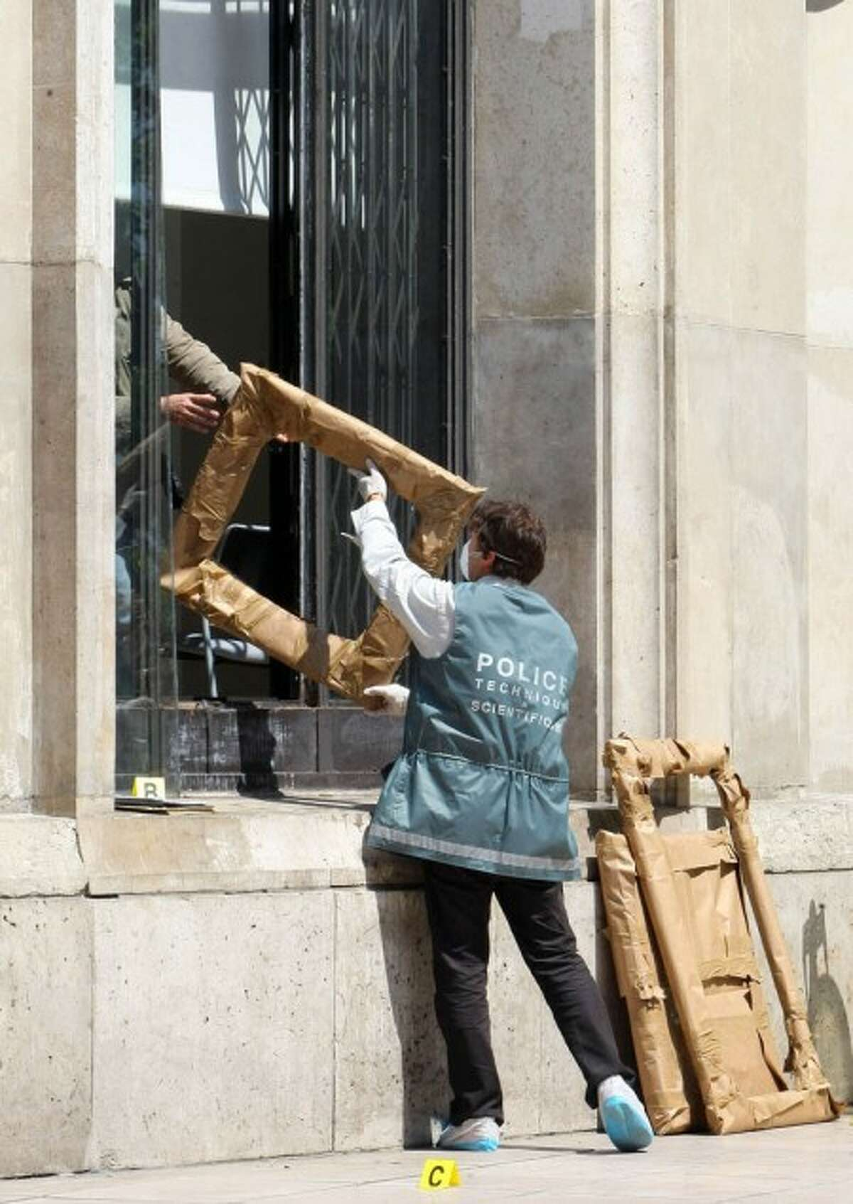 A police officer hands the packed frames of the stolen paintings, to a colleague, from outside the Paris Museum of Modern Art, following the stealing of five paintings Thursday May 20, 2010. Police and prosecutors say a lone thief has stolen five paintings worth a total of Euros 500 million ($613 million), including works by Picasso and Matisse. Other frames of the paintings arevisible at right. (AP Photo/Jacques Brinon)