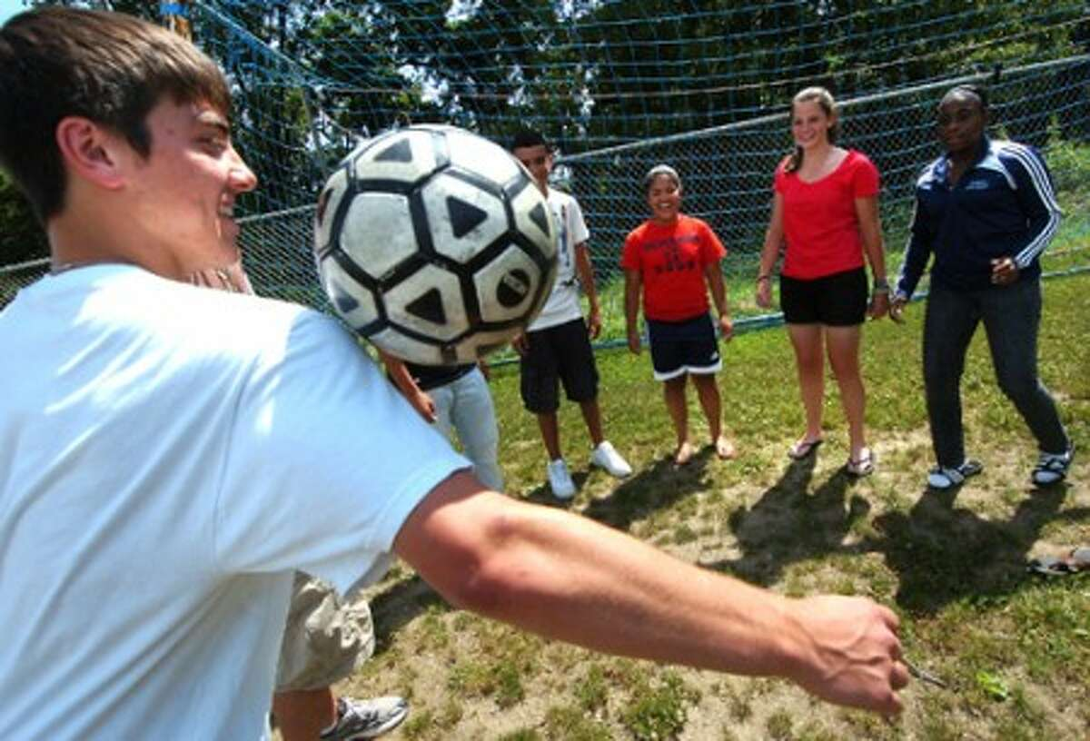 Photo/Alex von Kleydorff. Brien McMahon Jr.and soccer team captain, Alex Petridis juggles the soccer ball with players from the boys and girls soccer teams.