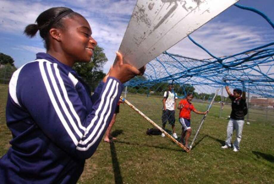 Photo/Alex von Kleydorff. Brien Mcmahon JR. Brittany Brim helps her fellow soccer players set up goals for a game during World Cup play.