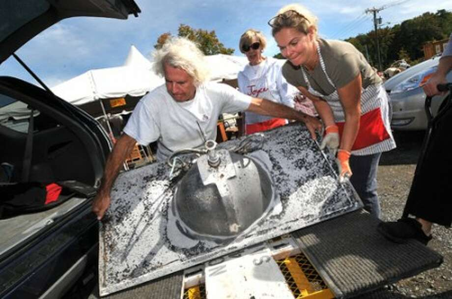 Photo/Alex von Kleydorff. Volunteer Ken Simene and Chairperson Michelle Doggett move a sink from the back of an SUV on thursday to prepare for this weekends Minks to Sinks sale in Wilton.