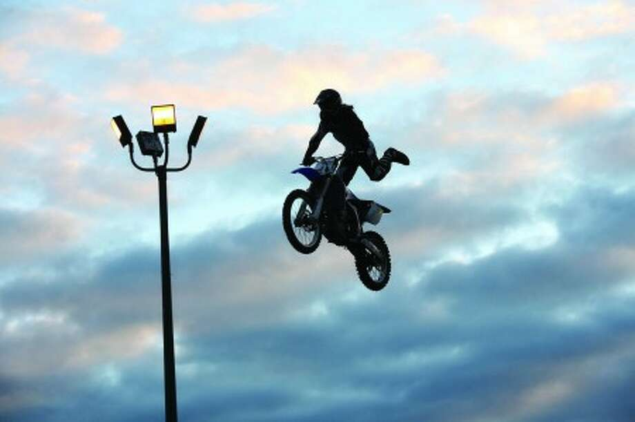 A Motorcrosser preforms for an audience during the Oyster Festival at Veteran''s Park in Norwalk Friday evening. Hour Photo / Danielle Robinson