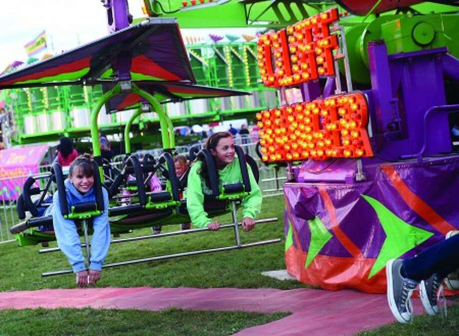 Lilliana Garcia and Tess St. John enjoy a ride on the Cliff Hanger at the annual Oyster Festival in Norwalk Friday evening. Hour Photo / Danielle Robinson