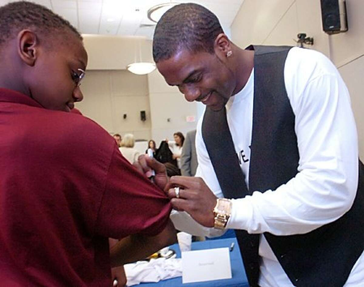 NY Jets star Jerricho Cotchery signs the shirt of Trailblazer Tylor Sanon at Stamford Hospital''s Tully Medical Center Friday afternoon. The United Way, Stamford Hospital, United Way and Cotchery teamed up in an effort to