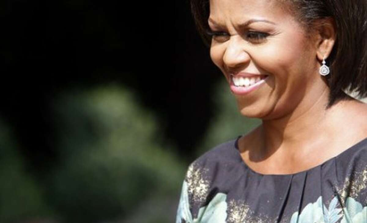 U.S. First lady Michelle Obama smiles as she poses for photographers during a luncheon at Stone Barns Center in Tarrytown, N.Y. , with some of the spouses of chiefs of state attending the United Nations General Assembly, Friday, Sept. 24, 2010. (AP Photo/Mary Altaffer)