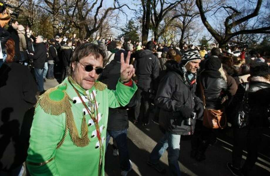 Raymond Brisson, left, of Cranston, R.I., dressed as John Lennon, flashes a peace sign as he joins the crowd at the Imagine mosaic in the Strawberry Fields section of New York''s Central Park, Wednesday, Dec. 8, 2010. (AP Photo/Richard Drew)