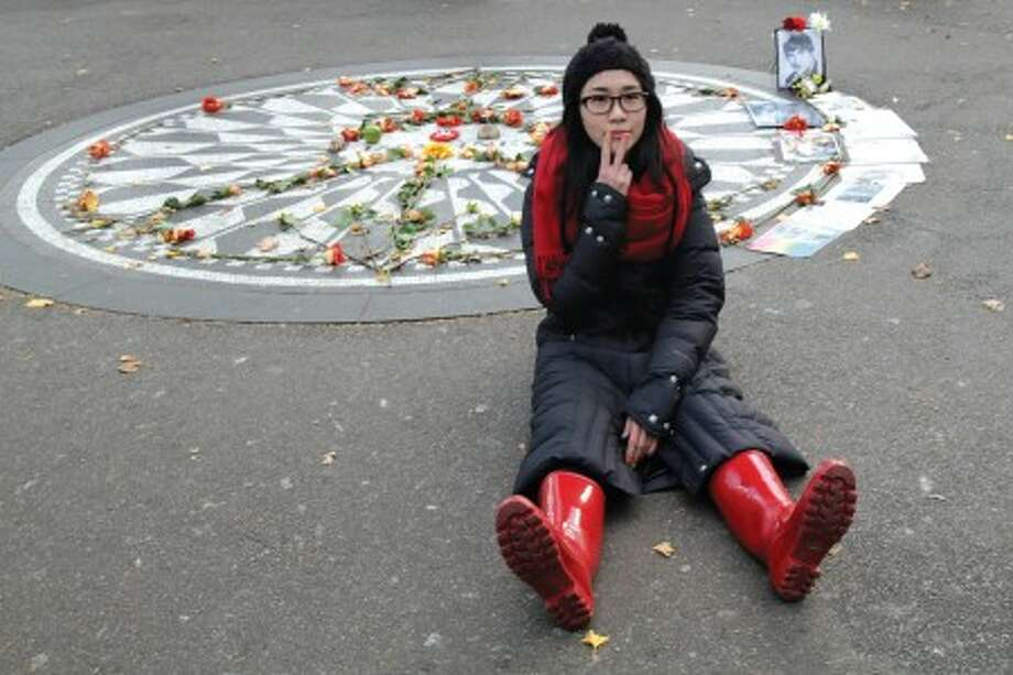 Chi Chi Yao, of Taiwan, makes a peace sign as she poses for photos at Strawberry Fields in New York''s Central Park, Tuesday, Dec. 7, 2010 in New York. Wednesday marks 30 years since John Lennon was murdered outside his New York apartment, triggering a wave of grief around the world. (AP Photo/Mary Altaffer)