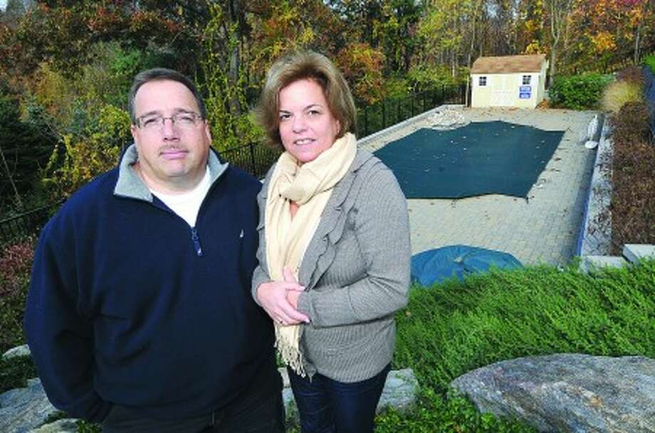 Photo/Alex von Kleydorff. Mitch and Iris Lasky stand near their new 18 X 36 Roman style pool that is built partially on neighbors property.