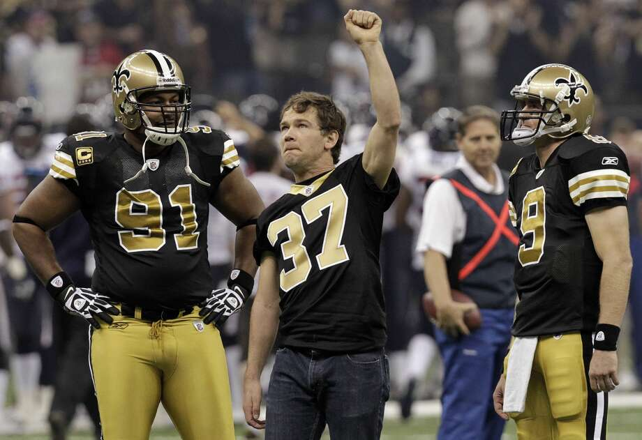In this Sept. 25, 2011, file photo, former New Orleans Saints football player Steve Gleason raises his hand to the crowd as Saint quarterback Drew Brees (9) and defensive end Will Smith (91) look on. Photo: Gerald Herbert/AP
