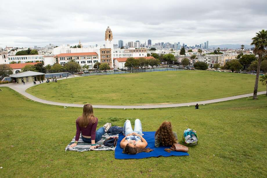 Abby Lowell (left), Katelyn Wong and Sofia Pelosi relax in Dolores Park, where a city notice offering reservations for picnic space ignited public outrage. Photo: Amy Osborne, Special To The Chronicle