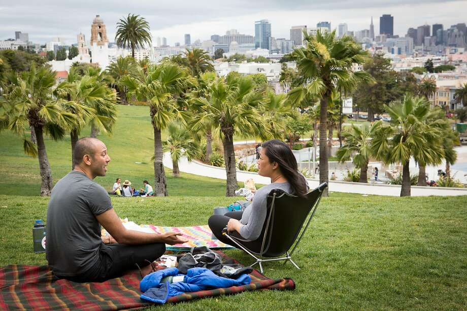 Jeff Bordey and Thia Letran enjoy a picnic at Dolores Park, where reservations have been available for private events such as weddings and reunions. Photo: Amy Osborne, Special To The Chronicle