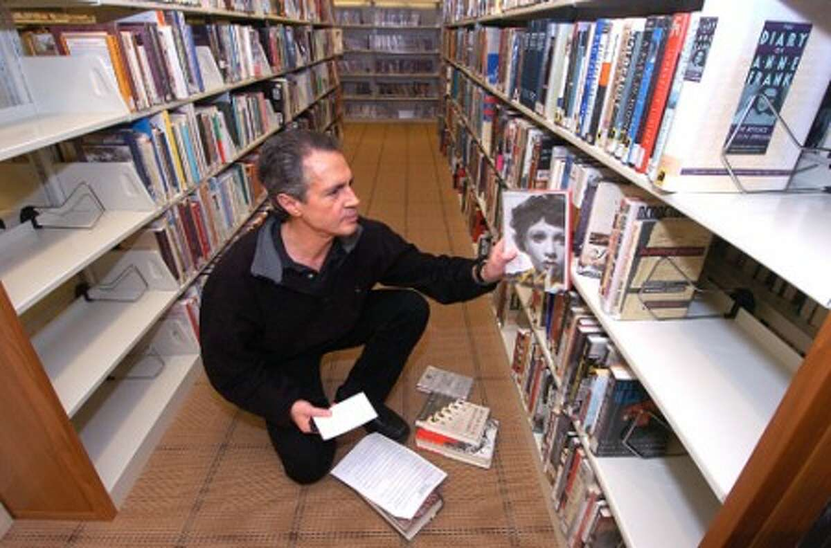 Photo/Alex von Kleydorff. Steve Mersereau looks through the Non Fiction area in the newly remodeled Ferguson Library