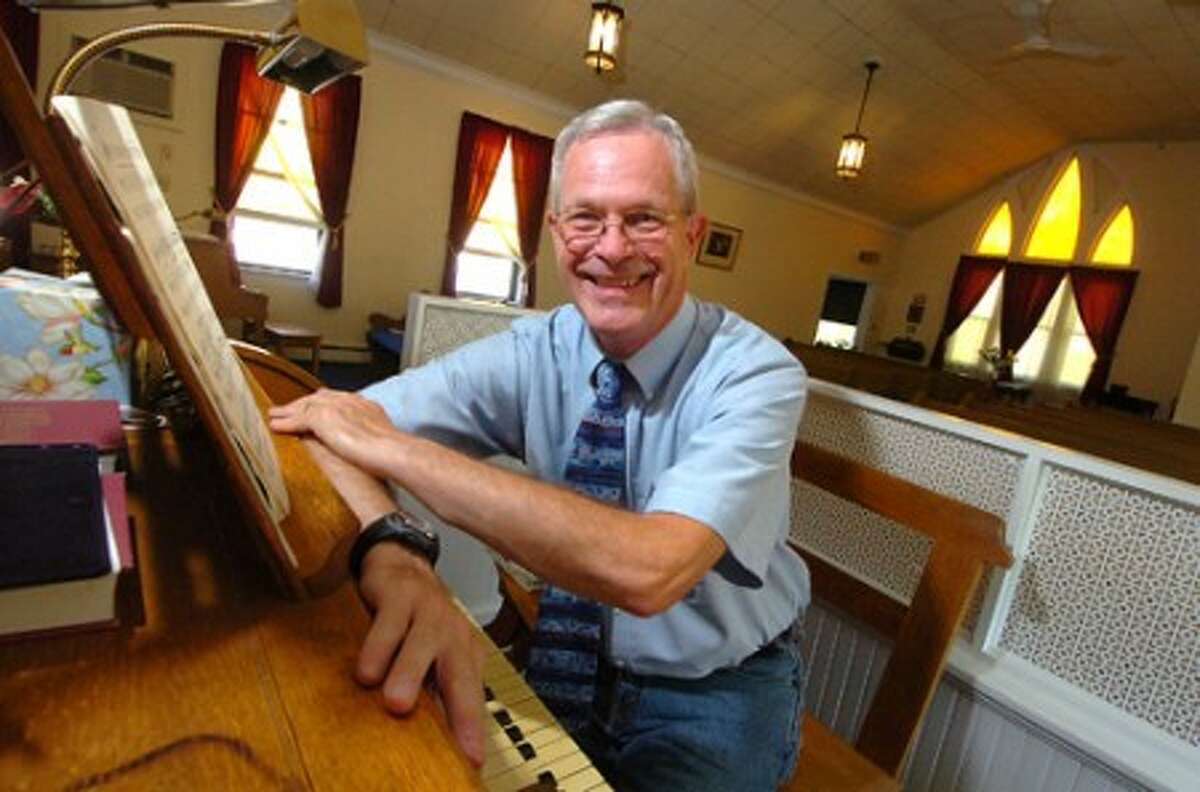 Photo/Alex von Kleydorff. Pastor Robert Story of The Community Advent Christian Church, at the original 1936 Estey pipe organ he plays.