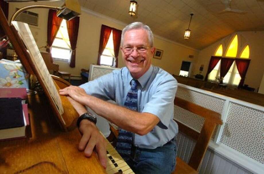 Photo/Alex von Kleydorff. Pastor Robert Story of The Community Advent Christian Church, at the original 1936 Estey pipe organ he plays.