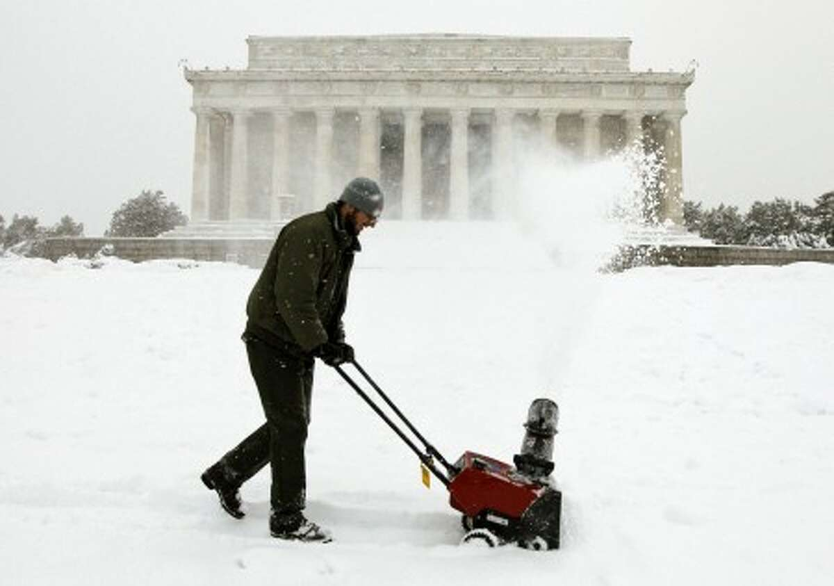 Jeff Gowen, with the National Park Service, uses a snow blower in front of the Lincoln Memorial as the snow continues to fall in Washington Wednesday, Feb. 10, 2010.(AP Photo/Alex Brandon)
