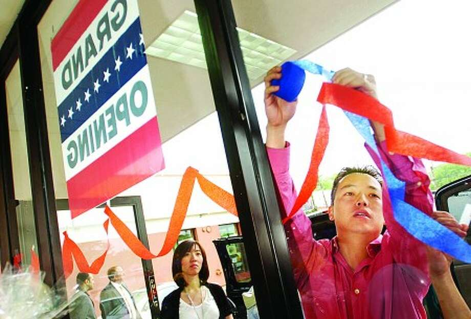 Matthew Wong puts up decorations for Norwalk Pharmacy''s Grand Opening ceremony Tuesday morning at the County Mall on Westport Ave. Hour photo / Erik Trautmann