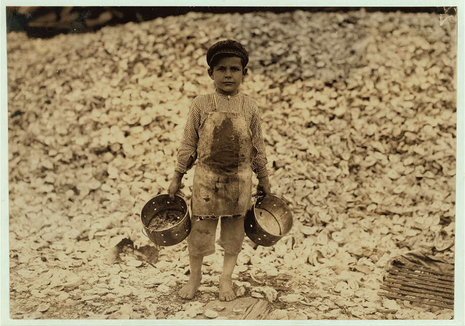 """Manuel, the young shrimp-picker, five years old, and a mountain of child-labor oyster shells behind him. He worked last year. Understands not a word of English. Dunbar, Lopez, Dukate Company. Location: Biloxi, Mississippi (February 1911)."" -Library of Congress. Photo by Lewis Wickes Hine. Photo: Library Of Congress, By Lewis Wickes Hine"