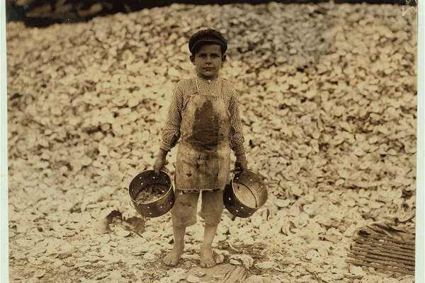 """Manuel, the young shrimp-picker, five years old, and a mountain of child-labor oyster shells behind him. He worked last year. Understands not a word of English. Dunbar, Lopez, Dukate Company. Location: Biloxi, Mississippi (February 1911)."" -Library of Congress. Photo by Lewis Wickes Hine."