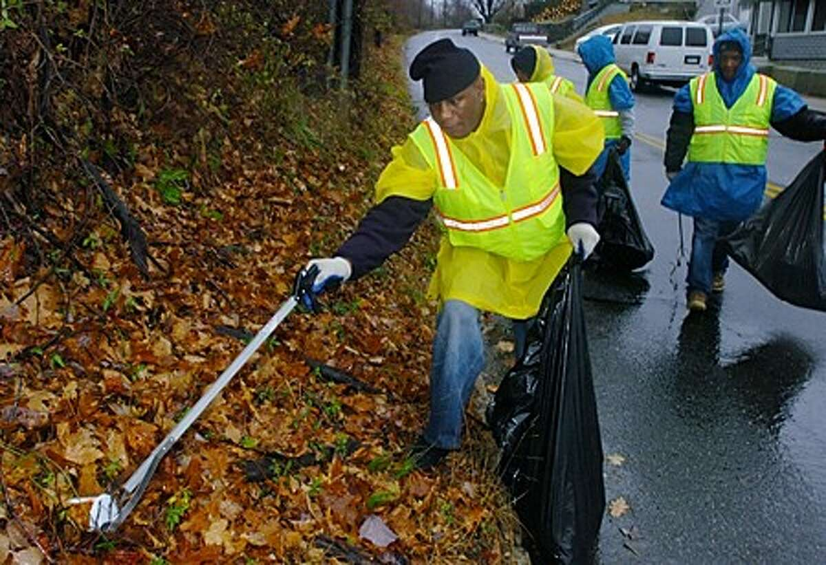 Clients of the Norwalk Emergency Shelter pick up trash along South Main as part of the HopeWorks program that provides work and job traing for the homeless. Hour photo / Erik Trautmann