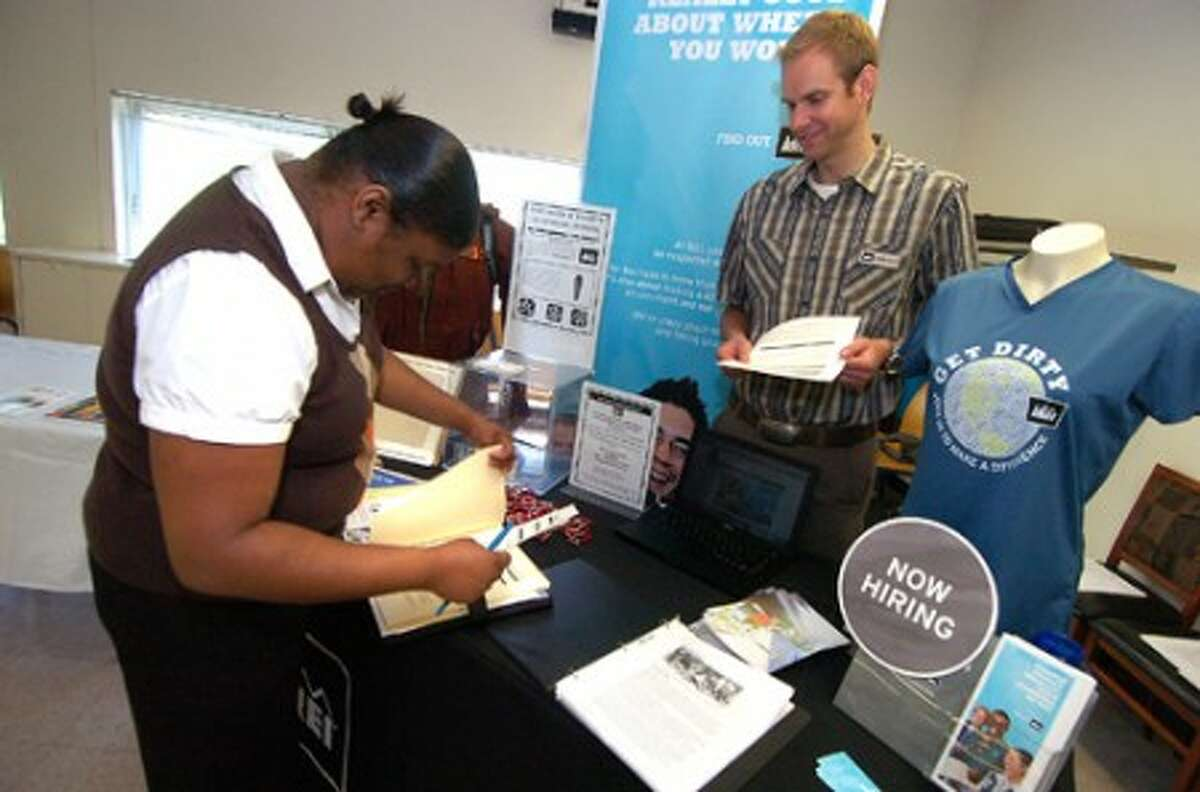 Photo/Alex von Kleydorff. Tyreda Sellers gives her resume to Jeremy Castle with REI during a NEON Job fair. REI, a sporting goods chain will be opening a Norwalk location in October on Connecticut Av.