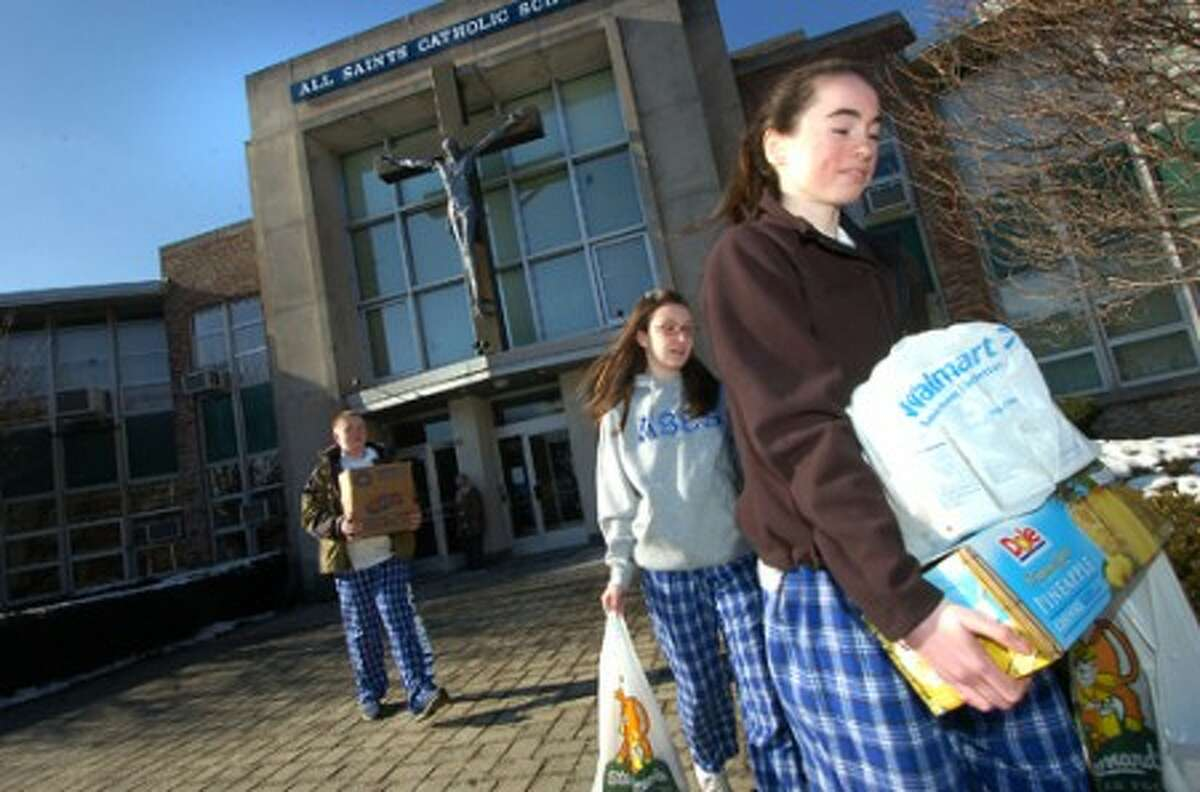 Photo/Alex von Kleydorff. 13 yr old All Saints School 8th Grader Colleen O''Neill carries some of the donated food to be delivered to the St Vincent De Paul Society.