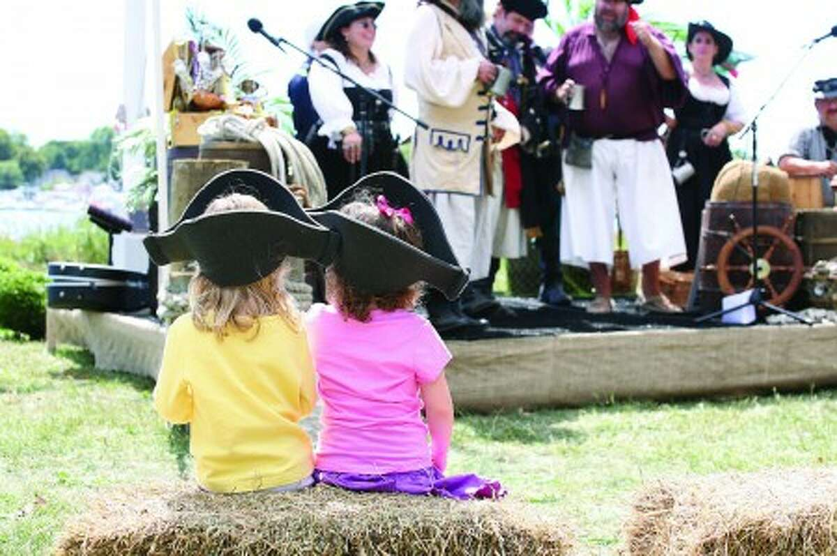 Two girls watch The Buccaneers sing pirate songs in their pirate hats at the Oyster Festival in Norwalk Saturday afternoon. Hour Photo / Danielle Robinson