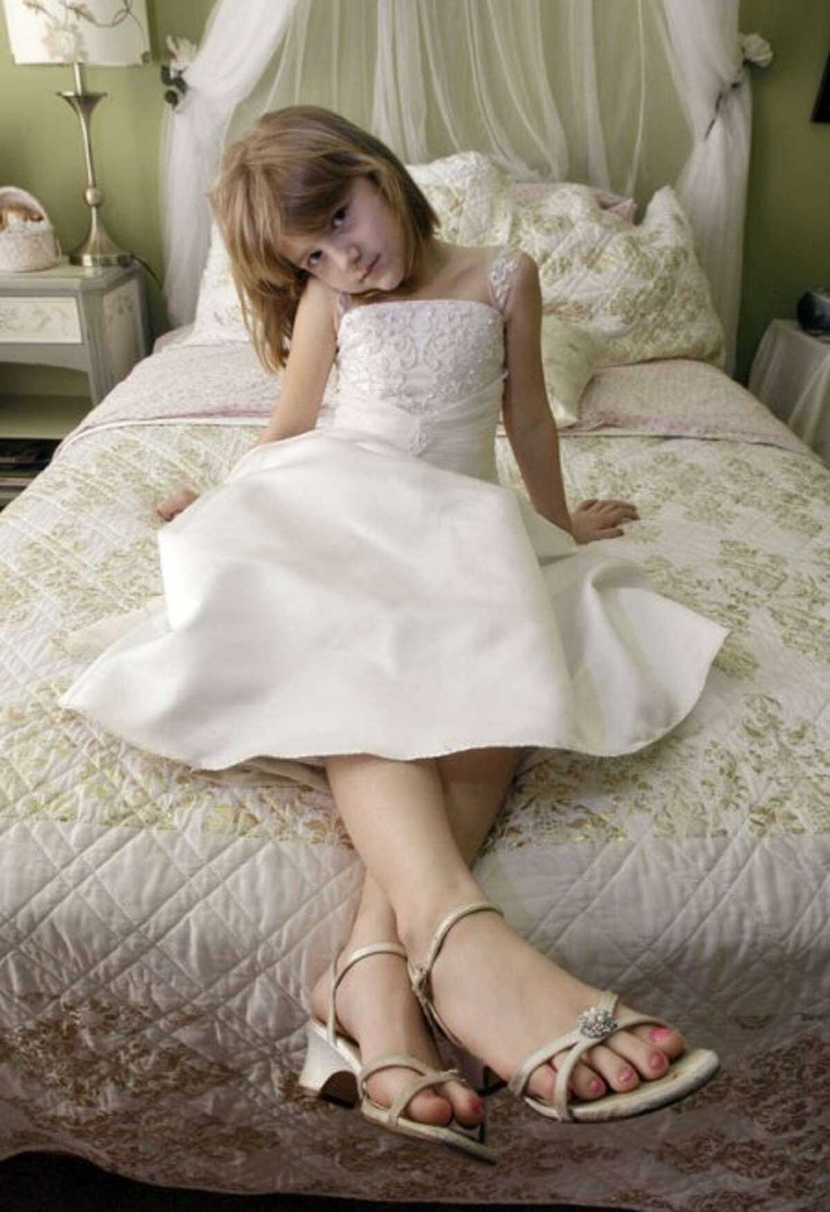 Six-year-old Helena Bell posses in her short high-heeled shoes at her home in Los Angeles Tuesday, Jan. 12, 2010. Helena first wore the heels as flower girl at a wedding about six months ago. Since then, she loves to wear the shoes - and her flower girl dress - to church on Sundays, and other