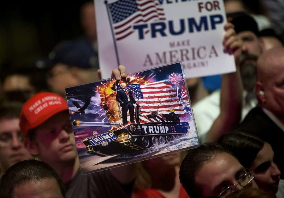 Trump-on-a-tank artwork in the crowd as  the presumptive Republican nominee spoke campaigned at Gilley's Club in Dallas, June 16, 2016. Donald Trump's campaign schedule is being driven by his fund-raising needs, prompting him to appear in heavily Republican states like Georgia and Texas and diverting his attention from battleground states where Hillary Clinton is spending her time. (Eric Thayer/The New York Times) Photo: ERIC THAYER, NYT