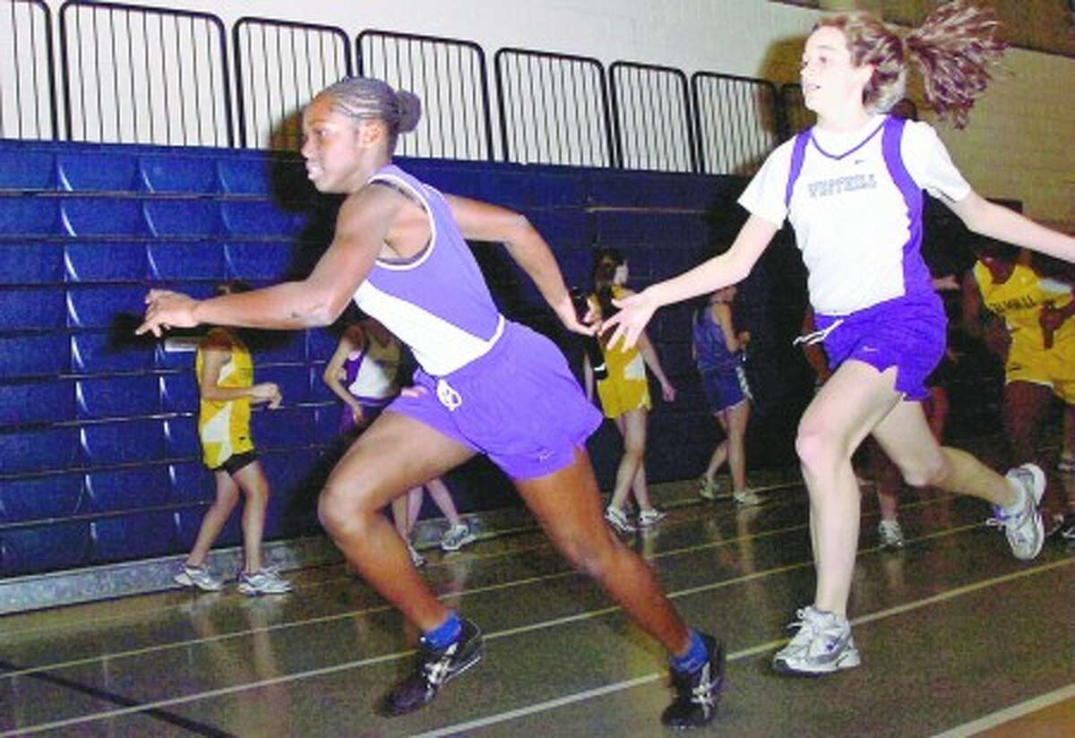 Westhill''s Nahama Pierre and Julia Busto particpate in the Sprint Medley during their indoor track meet in Wiltonn Saturday. Hour photo / Erik Trautmann