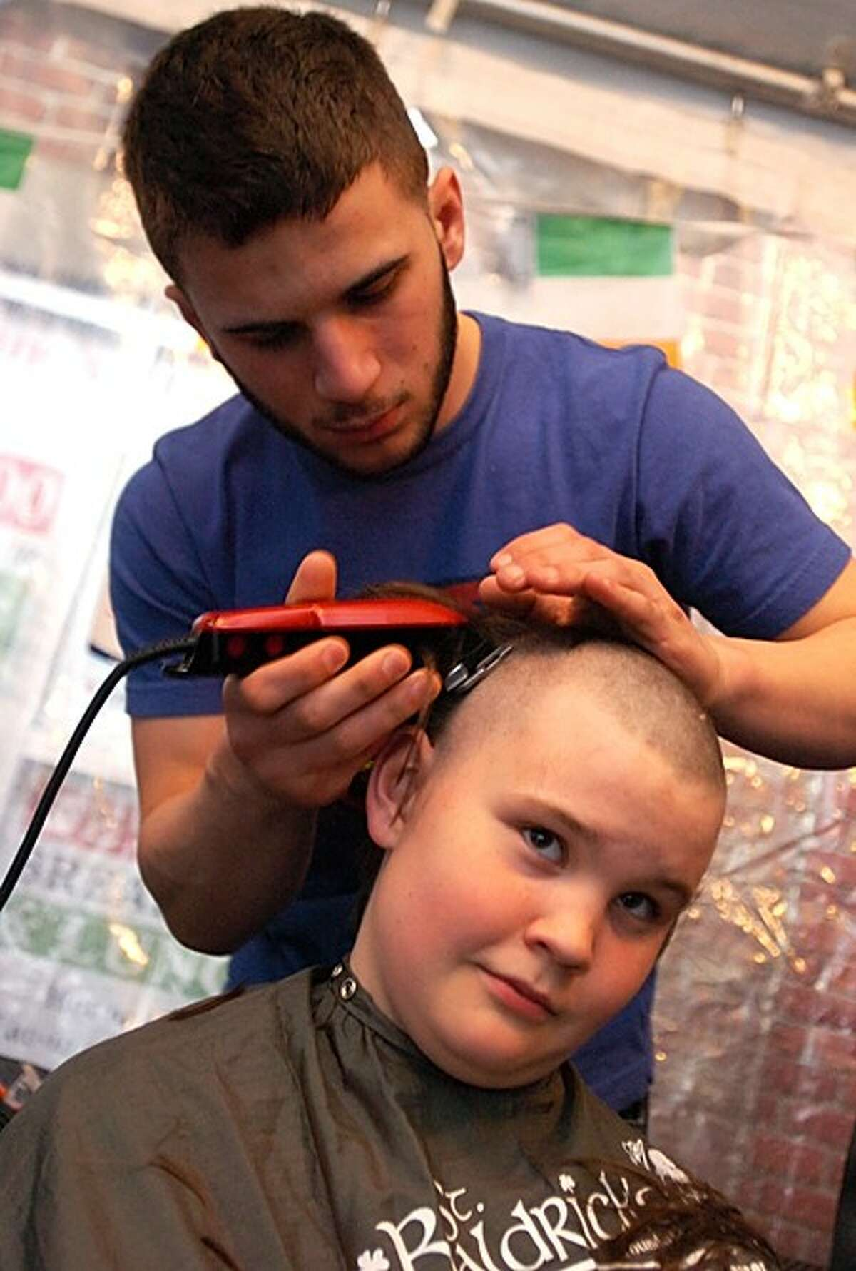 Zach Napolitano of SoNo Academy shaves the head of twelve year old Teague Whalen during the St. Baldrick''s benefit for kids with cancer at O''Neill''s Pub Saturday. Hour photo / Erik Trautmann